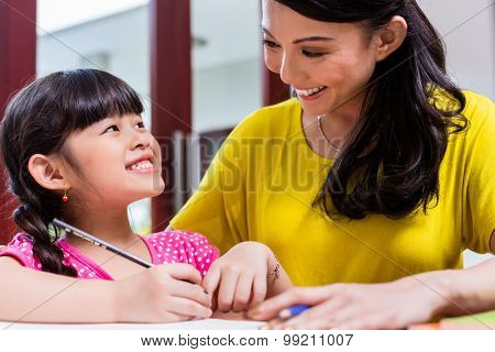 Chinese mother homeschooling her child teaching her daughter to write