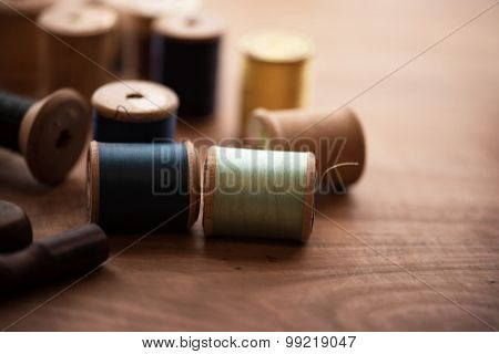 Old sew thread wooden reels or bobbins on a old grungy work table. Tailor's work table. textile or fine cloth making. Shallow depth of field.