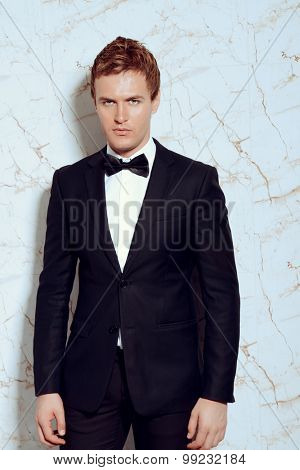 Vogue shot of a handsome man in black suit and bow-tie. Men's beauty, fashion.