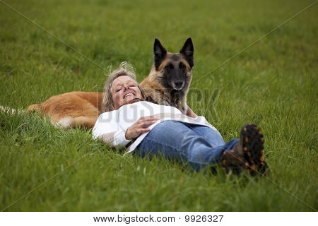 blond woman relaxing with her dog