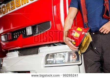 Midsection of male firefighter holding red helmet while leaning on firetruck at station