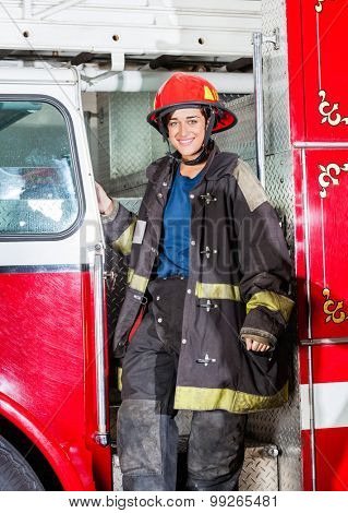 Portrait of happy female firefighter in uniform standing on truck at fire station