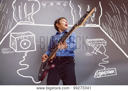 Teen boy playing guitar in the room are speakers synth rock conc