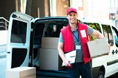 Colorful picture of courier delivers package. Courier holding the box and smiling. poster