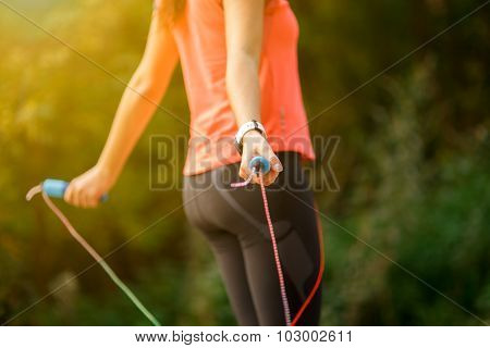 Close up of woman feet jumping, using skipping rope in park