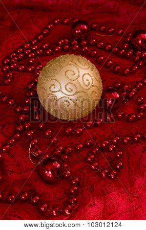 Christmas Decorations On A Red Background Accessories. Gold Ball Toy With Bright Lace.