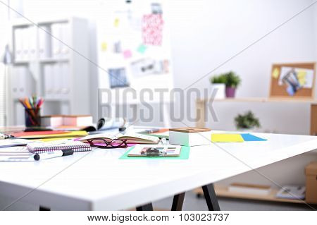Desk of an artist with lots of stationery objects. Studio shot on wooden background