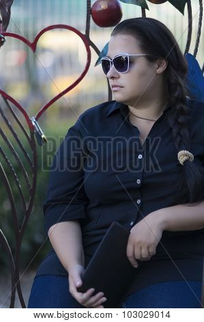 The Woman In Sun Glasses Sits On A Bench.