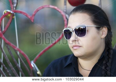 The Woman In Sun Glasses On A Bench.