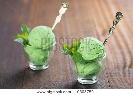 Scoop of matcha ice cream in cup on rustic old wooden vintage background.