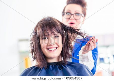 Female coiffeur blow dry women hair with blow dryer in shop