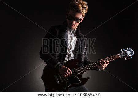 dramatic picture of a young rock and roll guitarist playing his electric guitar on black studio background