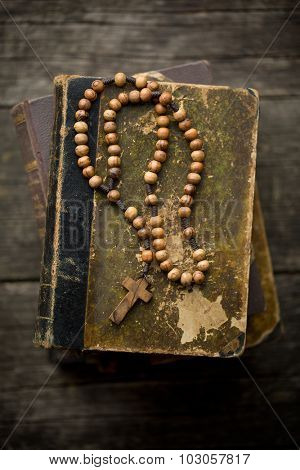 the vintage rosary beads on old book