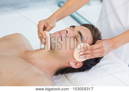 Close -up of a handsome young man receiving facial massage at spa center