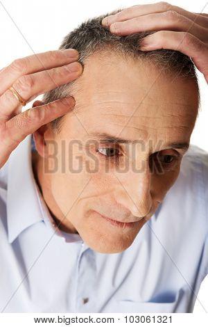 Mature man examining his hair.