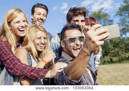 group of smiling friends taking selfie with smartphone