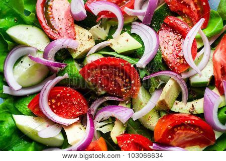 Salad with fresh vegetables on wooden rustic background. Salad with tomato, cucumbers, avocado and onion