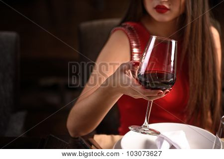 Chinese woman toasting at the restaurant with red wine and a glass