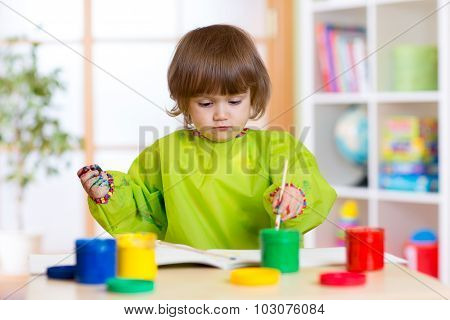 Child girl with hands painted color paints