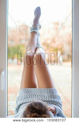 Young woman with beautiful legs wearing nordic print socks and knitted dress lying down at home by the window. Blurred garden fall background