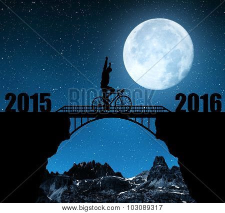 Cyclist riding across the bridge in night. Forward to the New Year 2016.