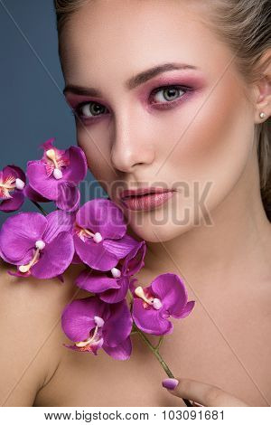 Portrait of a beautiful blonde woman with delicate makeup holding orchid in her hand close up. Fashion photo