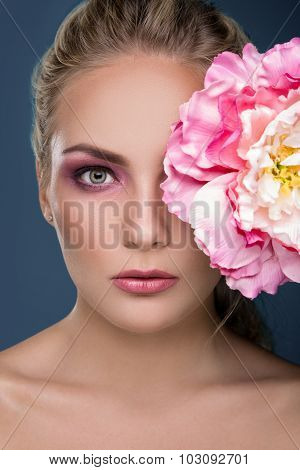 A close-up portrait of young girl with white and rosy peony near her face on blue background. Fashion photo.