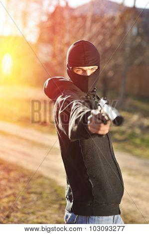 Gunman in black mask holding gun with silencer poster