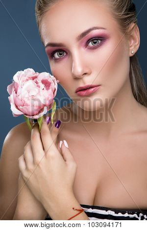 Beautiful young woman with sensitive makeup holding peony in her hand on blue background close up. Fashion photo.