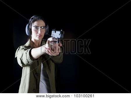Woman holding a gun with protective gear