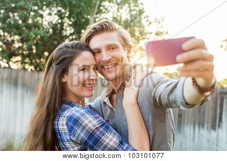 Couple taking a selfie with their cellphone outside
