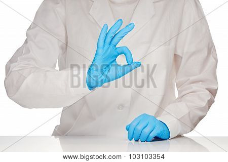 Close up of female doctor in white medical gown and blue surgical gloves showing OK sign