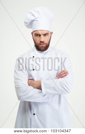Portrait of angry male chef cook standing with arms folded isolated on a white background
