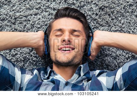 Portrait of a handsome man listening the music on the floor at home
