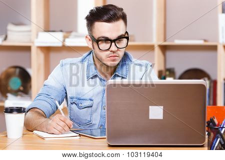 Handsome serious man wearing in casual blue shirt and glasses looking at laptop screen and writing something in his notebook on the bookshelves background waist up