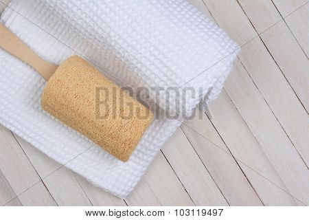 Overhead view of a loofah on a white towel on a white wood surface. Horizontal format with copy space.