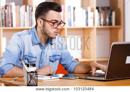 Portrait of concentrated man wearing in casual shirt sitting at the table and looking at the laptops screen on the bookshelves background waist up