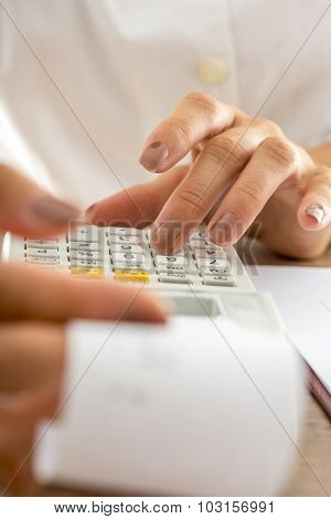 Front View Of Female Accountant Calculating With Adding Machine