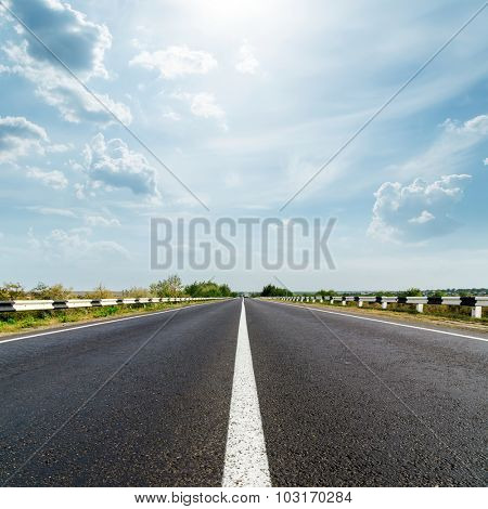 sun in dramatic sky over asphalt road