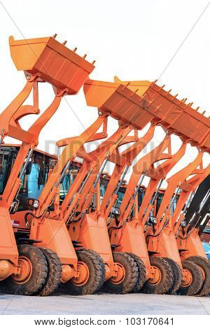 Row of heavy construction excavator machine against blue sky in