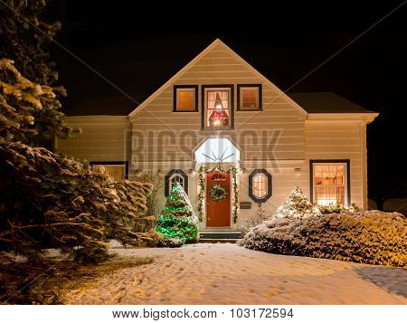 A house decorated with a wreath, garland and Christmas lights an a clear winter night.