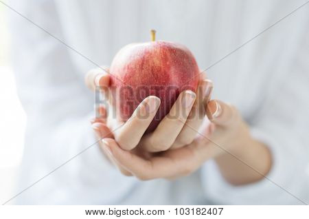 Closeup shot of a woman holding healthy red apple. Red apple in woman hands with white shirt at home. Shallow depth of field with focus on the red apple.