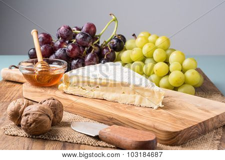Wooden Board With  Brie Cheese, Grapes, Nuts And Honey