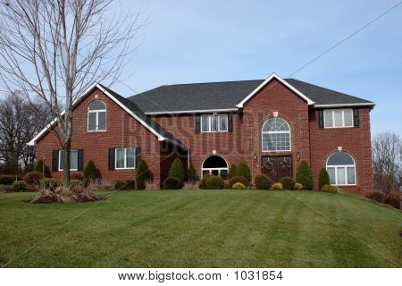 new luxury brick two story home with large landscaped front lawn. poster