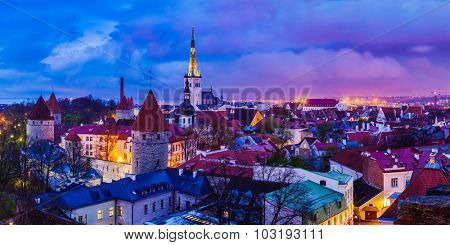 Panorama of aerial view of Tallinn Medieval Old Town with St. Olaf�¢??s Church and Tallinn City Wall illuminated in twilight, Estonia