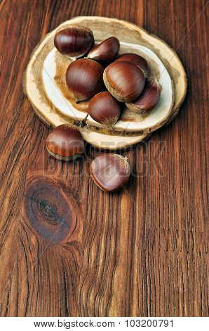 Raw chestnut on a wooden table, rustic style