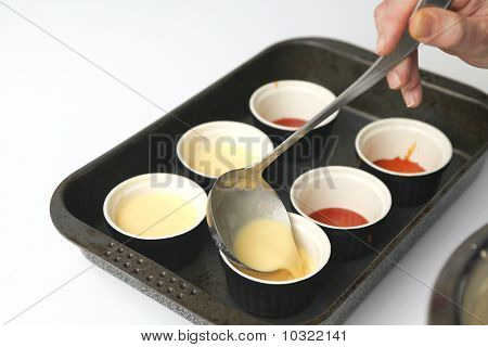 Pouring Creme On The Caramel In Pots