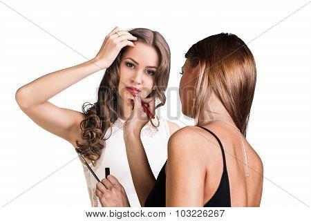 Make-up artist applying lip liner on model's lips