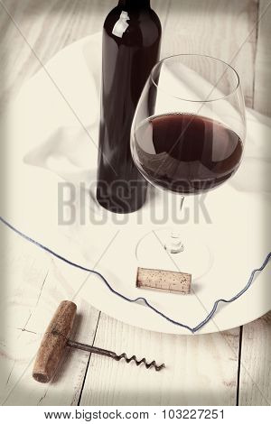 A retro looking wine still life with vignette. Glass of red wine, towel, old fashioned cork screw, cork and bottle in vertical format with instagram feel.