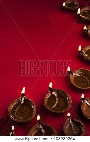 many beautiful diwali diya together on a red background, diwali greeting